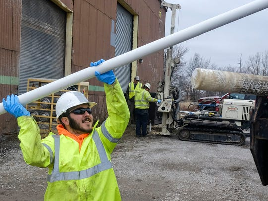 Rian Lopez from EnviroCore Inc carries a long pipe that served as a portion of a ground water well at the former Fairfield Engineering property on Tuesday morning. Lopez along with his coworkers will be spending the rest of the week digging up other such ground water wells in and around the property.