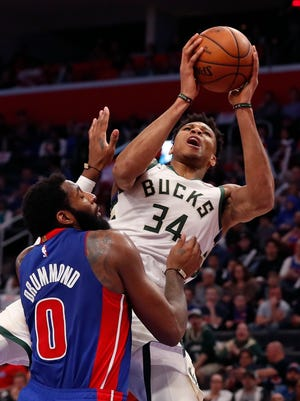 Bucks forward Giannis Antetokounmpo is fouled by Pistons center Andre Drummond  during the first half Monday night.
