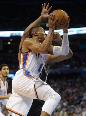 Oklahoma City Thunder guard Russell Westbrook drives to the hoop with San Antonio Spurs forward Tim Duncan defending him.