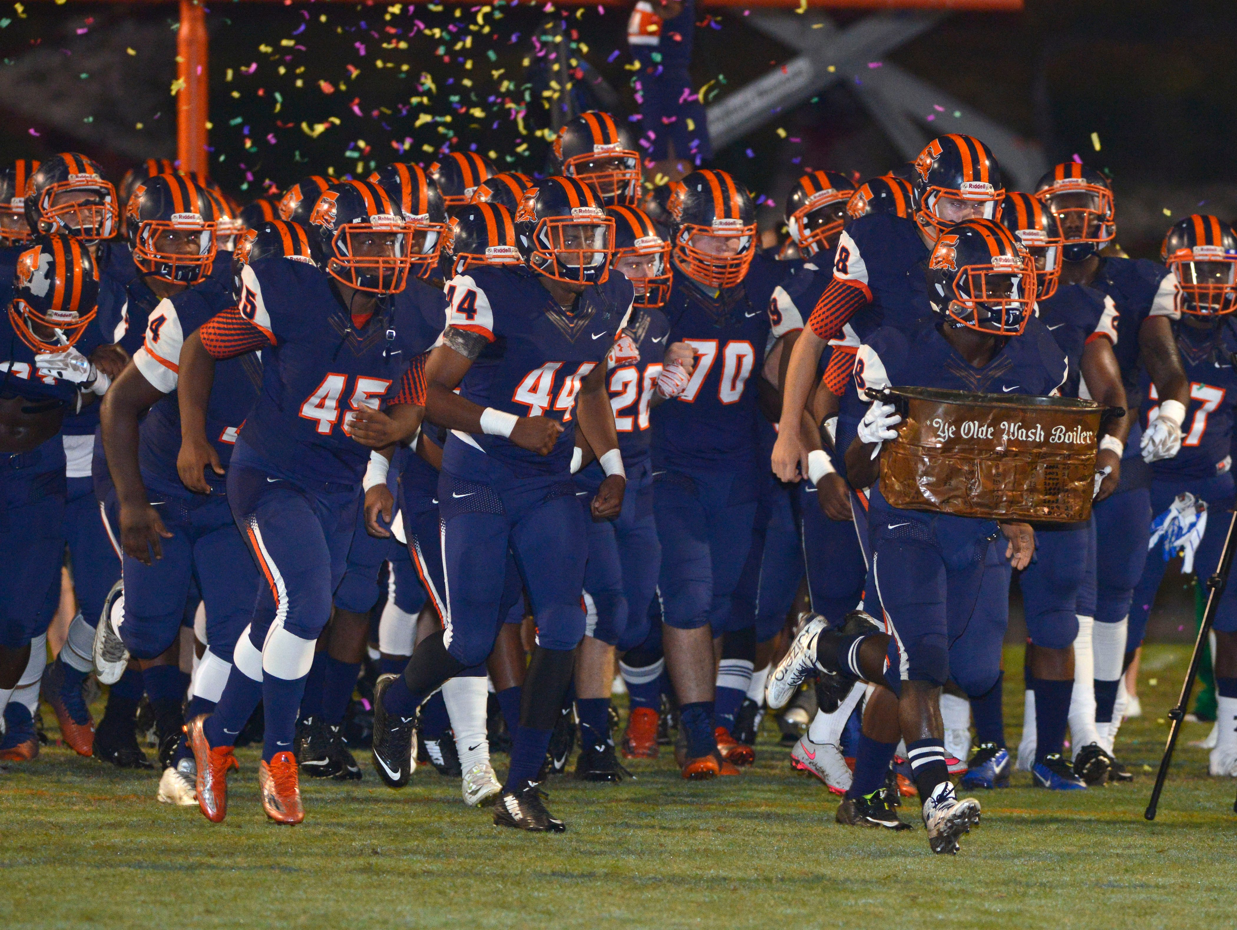 Escambia's Jabir Frye brings out Ye Olde Wash Boiler during the Escambia High and Pensacola High School football rivalry at Escambia High School. Some coaches are worried that these traditional rivalries may disappear if the FHSAA's new playoff proposal is passed.