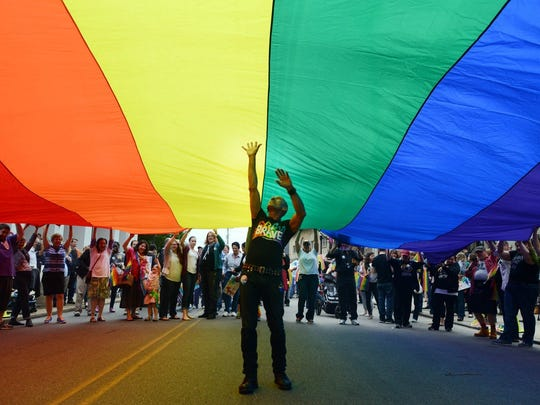Richard Parsakian lifts up from underneath a large pride banner to celebrate a federal judge ruling Pennsylvania's ban on same-sex marriage unconstitutional in Pittsburgh, Pa., on Tuesday.