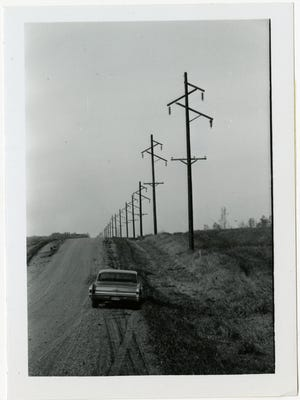 Poles along a country road before wires were attached.