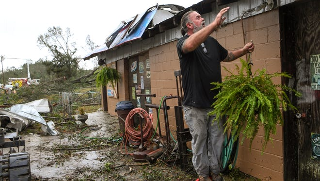 """Chuck King of Central places a hanging fern basket on his building along Robinson Bridge Road Monday. """"We're going to make this thing better,"""" King said of cleaning up after the storm described as a tornado in Pickens County."""