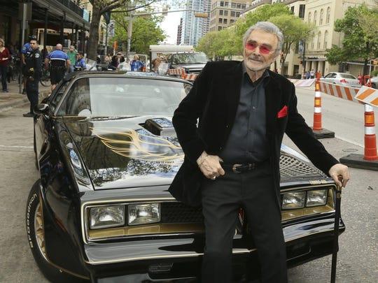 Burt Reynolds, sitting on a 1977 Pontiac Trans-Am at