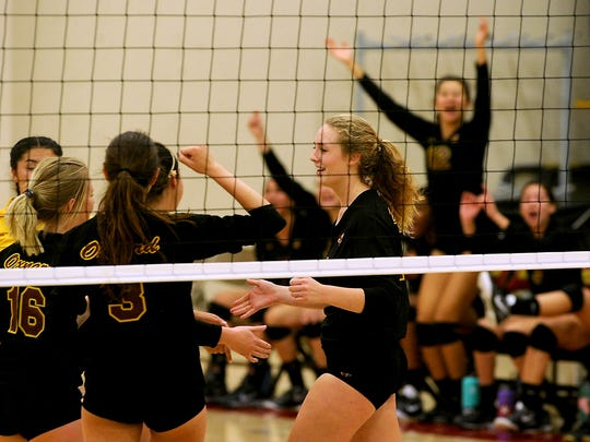 Oxnard High's Nicole Huelskamp, right, celebrates with her teammates after hitting a kill  in the first game of their CIF Division 4 playoff match against Bishop Montgomery at Oxnard Tuesday night.