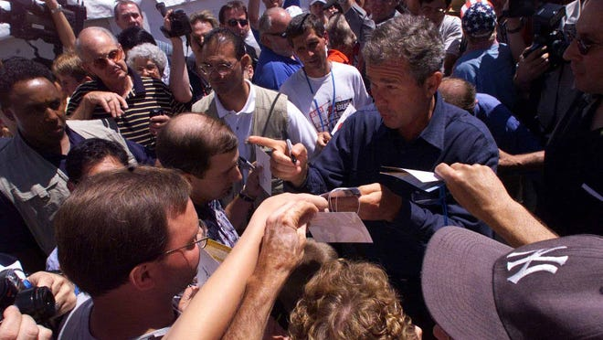 Then-candidate George W. Bush is swarmed by people at Hilton Coliseum in Ames on Aug. 14, 1999, during the Iowa Straw Poll.