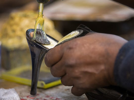 Clarence Howell, 78, fixes a heel at his shop, Clarence