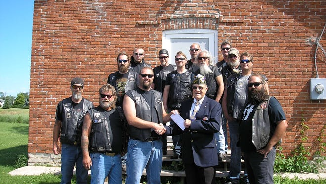 Devil's Knights Motorcycle Club gives a $4,000 check to Joe Heilman, chairman of the Door County Veterans Service Council.