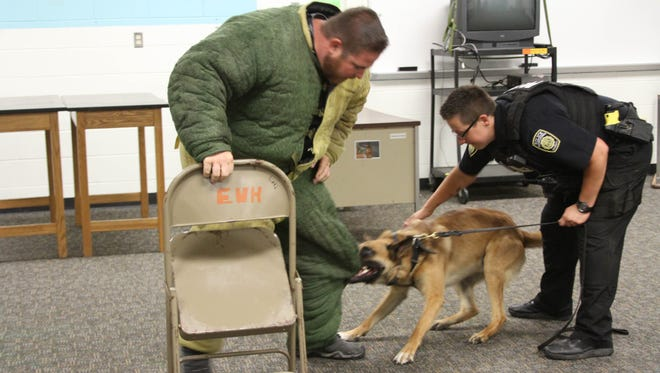 """Officer Bridget Bofysil with the Eastern Michigan University Police Department talks quietly to her K-9 partner, Nitro, as he holds the """"bad guy"""" during a training session at the Maltby Intermediate School on Bauer Road in Brighton. Nicholas King, owner of Von Der King Kennels & Training, played the """"bad guy."""""""