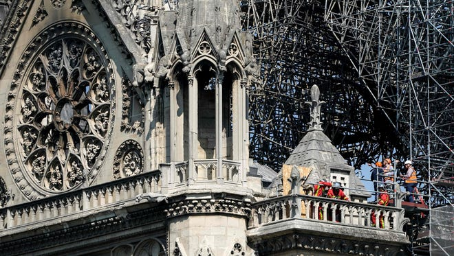 Firefighters and technicians work on a balcony of Notre-Dame de Paris Cathedral in Paris, four days after a fire devastated the cathedral. Thousands of Parisians and tourists watched in horror from nearby streets on April 15 as flames engulfed the building and rescuers tried to save as much as they could of the cathedral's treasures built up over centuries.