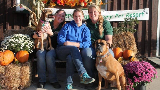 (From left) Lisa Vogt with Luna; Jane Medio; and Danielle Ford, owner of Pampered Pup, with Duke, are pictured at Barktoberfest, a fundraiser for TLC Animal Rescue.