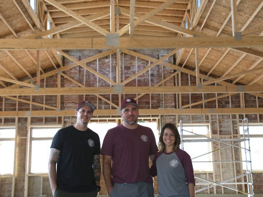 Casey Cooke (left to right) stands with Ben and Kim Ferguson in the new space that will host Village Point Market in Hayesville. The market will move across the street to this new building, while the old building will be converted into a ice cream/pizza shop run by the market.