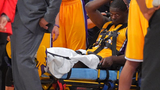 Los Angeles Lakers forward Julius Randle, right, sits on on a stretcher after Randle injured himself on a play during the second half of an NBA basketball game, Tuesday, Oct. 28, 2014, in Los Angeles.
