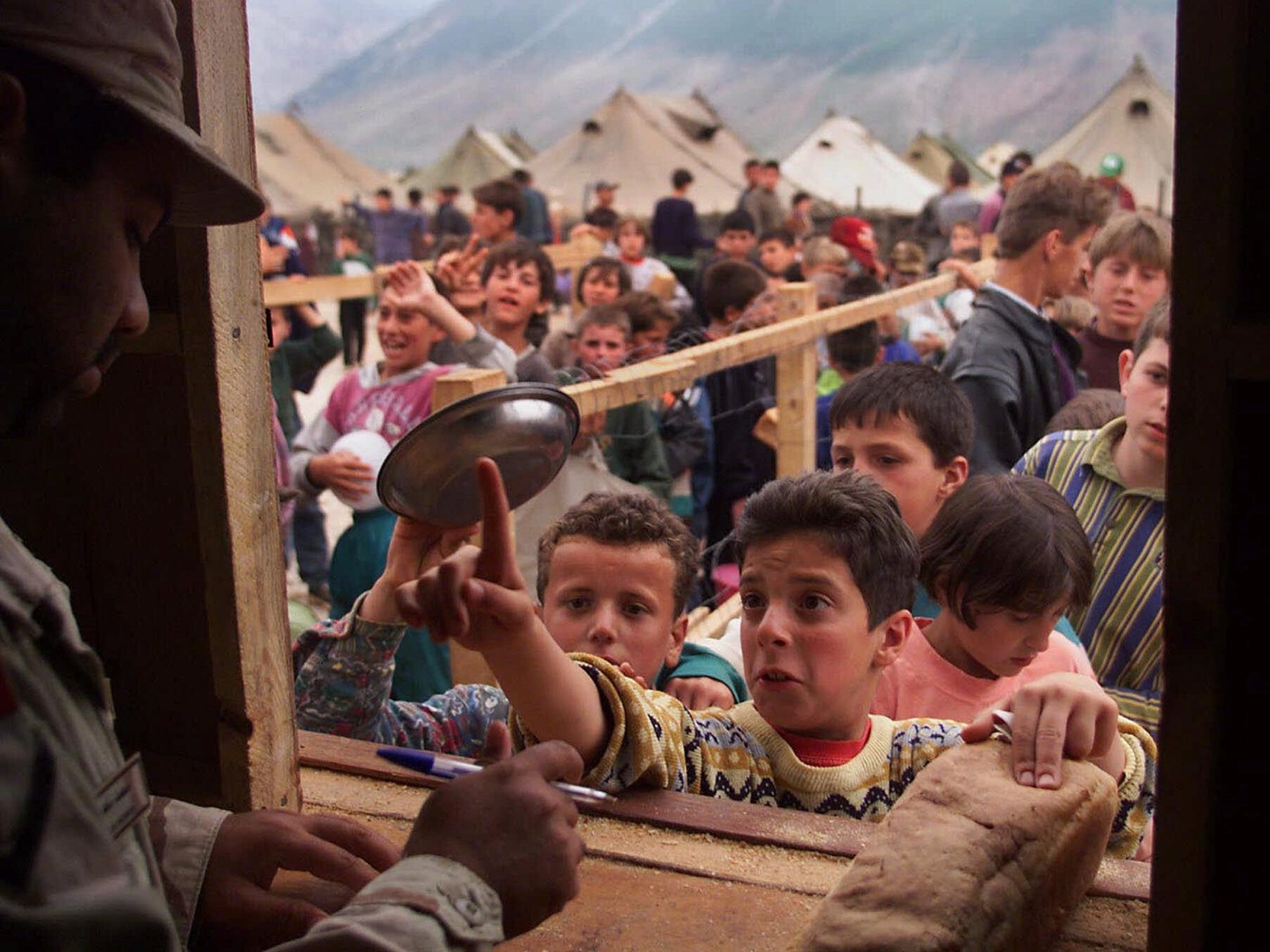 Ethnic Albanian refugees from Kosovo line up for bread at the United Arab Emirates-run camp in Kukes, Albania on May 17, 1999.