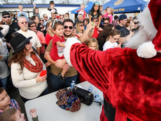Santa (Bruce Wessel of Manville) greets Layla Jones, 3, of Hillsborough, held by her father, Mike Jones as he arrives by airplane at Central Jersey Regional Airport in Hillsborough on December 13, 2015 sponsored by TriState Aviation, the flight school at the airport, along with Hillsborough Rotary Club.