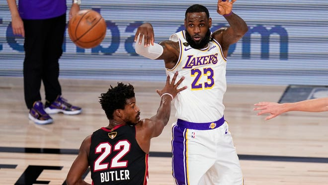 The Lakers' LeBron James passes the ball past the Heat's Jimmy Butler (22) during the first half of Game 6 of the NBA Finals on Sunday night.