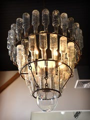 A chandelier made of bottles hangs from a remodeled