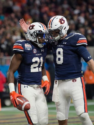 Auburn running back Kerryon Johnson (21) is greeted by Auburn quarterback Jarrett Stidham (8) after scoring a touchdown during the first half of the Peach Bowl between Auburn and Central Florida on Monday, Jan. 1, 2018, at Mercedes-Benz Stadium in Atlanta, Ga.