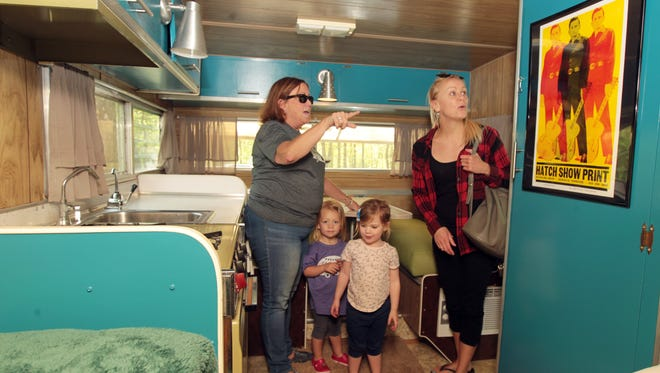 Kim Snider (left), who rented two vintage camping trailers for a weekend at Miami Whitewater Forest with her daughters and grandchildren, shows her daughter, Megan Bertram and grandchildren, Harper Szary, 2, and Mady Kuhlman, 3, the interior of a 1969 Lo Liner Aristocrat trailer.