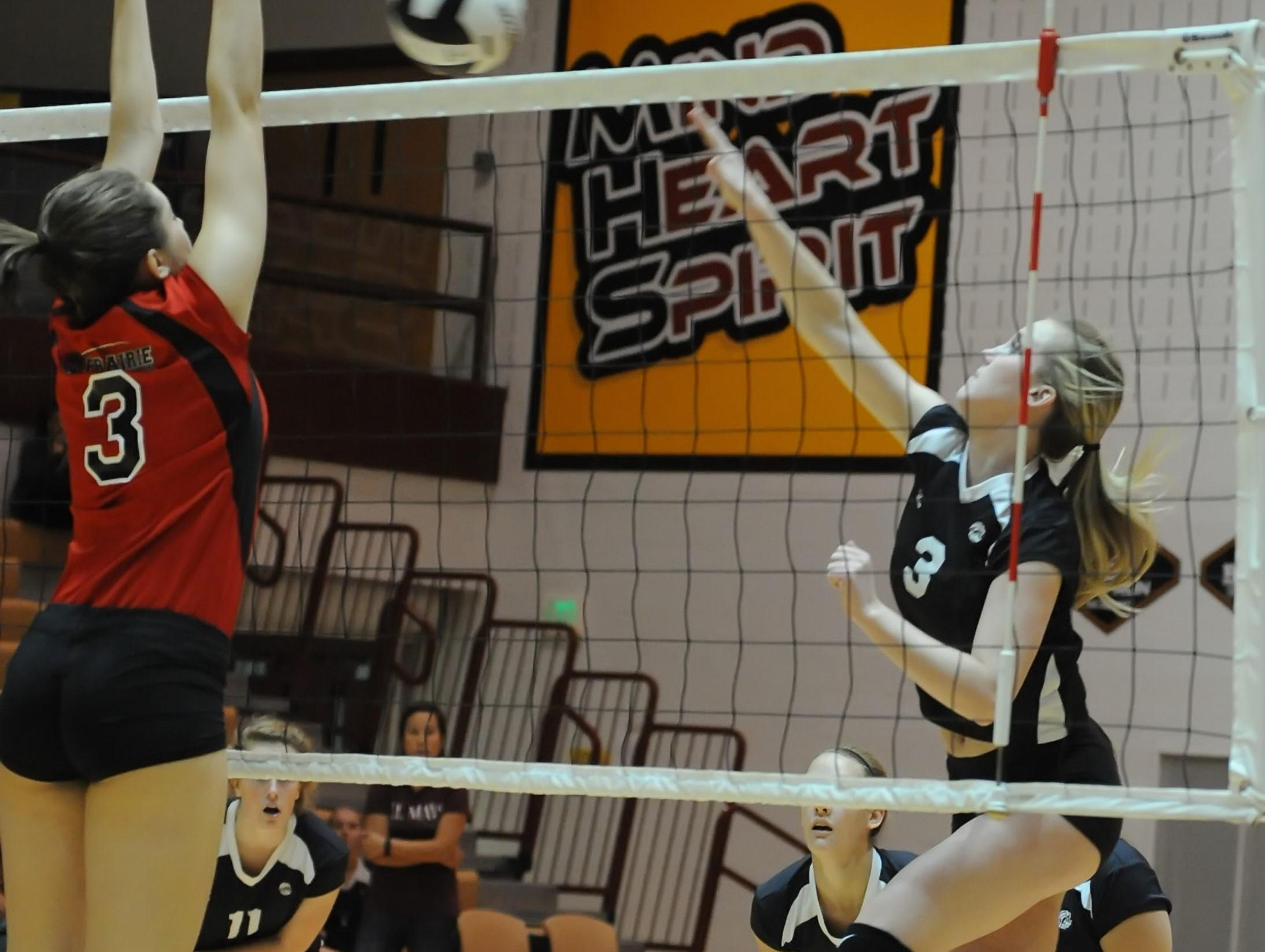 Clinton Prarie's Kayleigh Pletch fights to block Maverick junior Maddie Tracer Tuesday night.