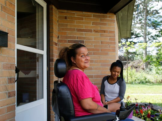 Shylah Outlaw and 16-year-old Tamara Outlaw on the front porch of their new home on Lansing's west side Tuesday, June 21, 2017.  Mother and daughter shared a bout with homelessness last spring.  Shylah has multiple sclerosis and uses a wheelchair.  They were homeless for about six months.  Tamara turned to social media in a plea for help after her mother attempted suicide.  With the help of friends, family, local homeless agencies, and the kindness of strangers, the two found permanent housing.