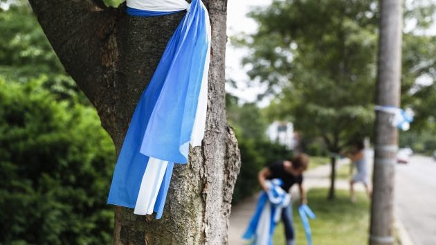 Alison Lebrun, center background, helps tie blue-and-white awareness ribbons along Springfield Pike near the family home of Otto Warmbier, a 22-year-old University of Virginia undergraduate student who was imprisoned in North Korea in March 2016, in the Wyoming suburb of Cincinnati on Tuesday, June 13, 2017. Warmbier, serving a 15-year prison term for alleged anti-state acts, was released and medically evacuated from the reclusive country Tuesday and has been in a coma for months, his parents said.