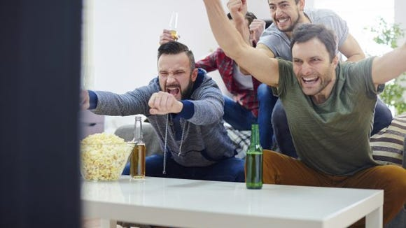 men watching tv cheering