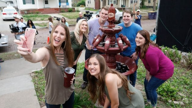 Claire Daniels, senior at Kansas State University, left, and her friends take a selfie after the unveiling of Daniels' very own Dr Pepper fountain on Thursday, April 13, 2017, in Manhattan, Kan. Dr Pepper surprised Daniels with the fountain after seeing a tweet from her.