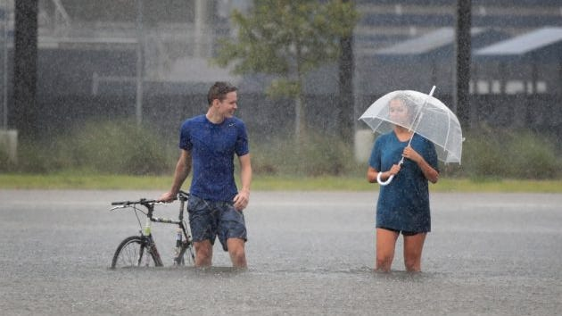 Cade Ritter (left) and Mari Zertuche walk through a flooded parking lot on the campus of Rice University after it was inundated with water from Hurricane Harvey on August 27, 2017 in Houston, Texas.