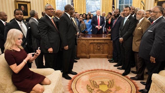 Counselor to the President Kellyanne Conway (L) checks her phone after taking a photo as President Trump and leaders of historically black universities and colleges pose for a group photo in the Oval Office of the White House before a meeting with Vice President Mike Pence Feb. 27, 2017.