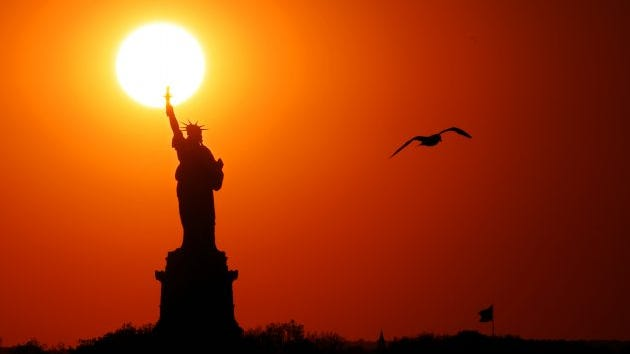 The sun sets behind the Statue of Liberty, June 02, 2017 in New York City.