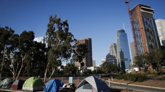 Tents housing homeless people are dwarfed by tall buildings in Los Angeles, Calif. A recent survey found 20% ofLos Angeles community college students are homeless.