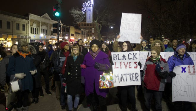"""Protesters hold signs bearing the """"BlackLivesMatter"""" hashtag during a protest Thursday on the University of Iowa Pentacrest."""