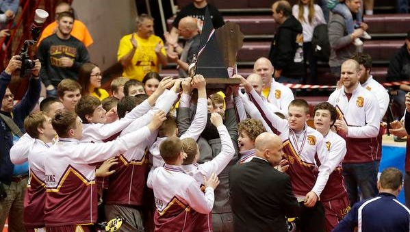 Luxemburg-Casco wrestlers and coaches hold up their trophy after winning the state title against Ellsworth on Saturday in the WIAA Division 2 state championship match in Madison.