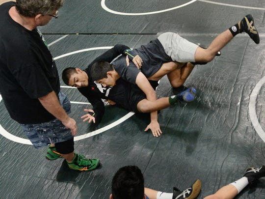 Andrew Rodriguez, left, a Pacifica High School wrestler and his brother Samuel, an assistant coach, demonstrate a technique at practice as Todd Stoke, standing, also an assistant coach, observes.