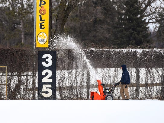 Groundskeeper Tim Kuhl blows snow off the warning track