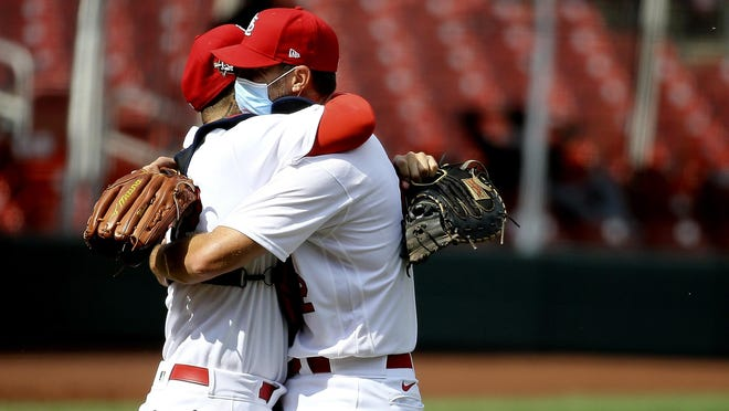 St. Louis Cardinals' Yadier Molina, left, celebrates with pitcher Adam Wainwright after his complete-game victory over the Cleveland Indians on Sunday in St. Louis.
