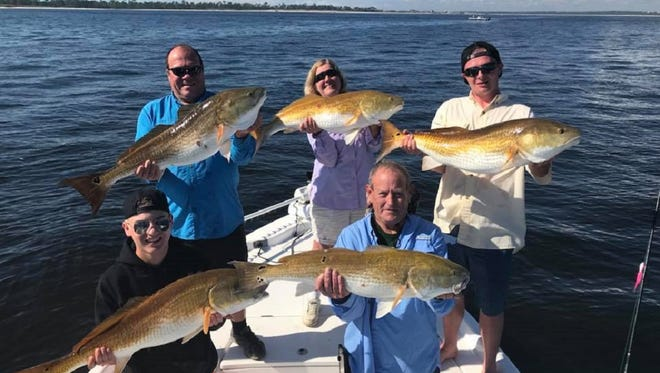 A group of happy anglers while on a redfish charter with local Captain Brett Tennant of Bout Time Charters based out of Pensacola.