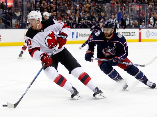 New Jersey Devils forward Jimmy Hayes, left, controls the puck against Columbus Blue Jackets forward Nick Foligno during an NHL hockey game in Columbus, Ohio, Tuesday, Dec. 5, 2017. The Devils won 4-1. (AP Photo/Paul Vernon)