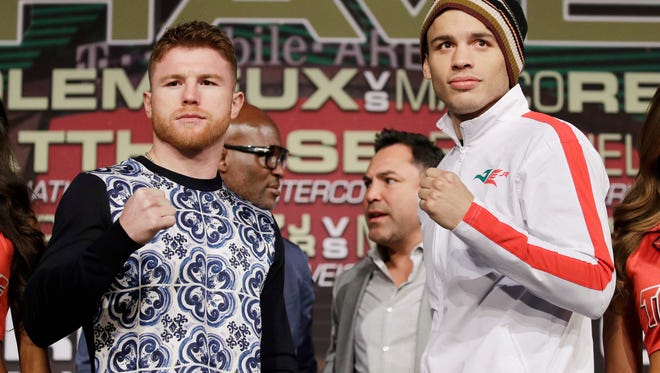 Canelo Alvarez, left, and Julio Cesar Chavez Jr. pose for photographers during a news conference Wednesday in Las Vegas. The two are scheduled to fight Saturday.