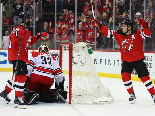New Jersey Devils right wing Kyle Palmieri (21) and New Jersey Devils left wing Taylor Hall (9) celebrate Palmieri's goal during the second period of their game against the Carolina Hurricanes at Prudential Center on Thursday, Feb. 15 2018 at Newark.