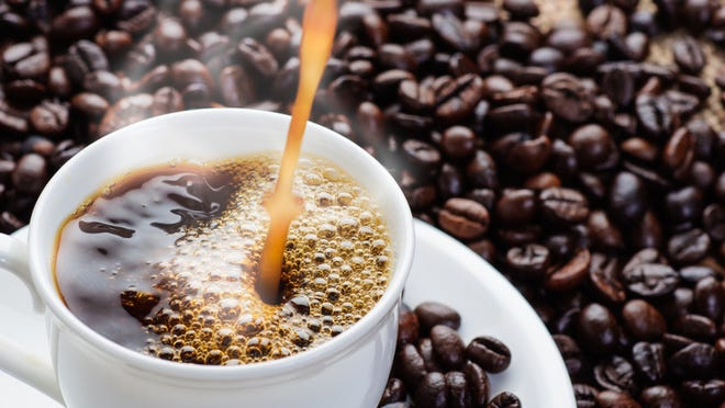 Close-up of steaming coffee being poured into a white coffee cup sitting on a saucer with coffee beans scattered on surface in background.