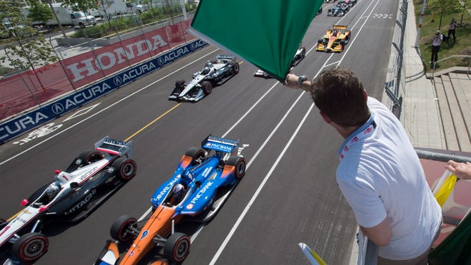 In this July 15, 2018, file photo, Jason Priestley waves the green flag to start an IndyCar auto race in Toronto. The stars of IndyCar were in Florida preparing to start their season when the coronavirus pandemic slammed the brakes on those plans 48 hours before the green flag.  Almost three months later, the series is finally set to go racing.  The 2020 season will open Saturday night, June 6, 2020, at Texas Motor Speedway in NBC's first ever primetime IndyCar race.