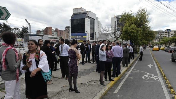 People remain in the street after a quake in Quito