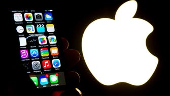 This file photo taken on January 30, 2015 shows an iPhone next to the Apple logo in Lille, France.