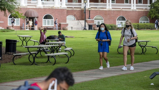 Georgia College and State University freshmen Ashlynn Anglin, right, and Meghan Murphy, second from right, wear face masks as they talk amongst themselves while walking through the campus in Milledgeville.