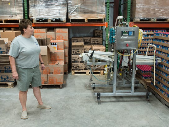 Lori Clough, Owner/Manager of 3rd Wave Brewing, stands