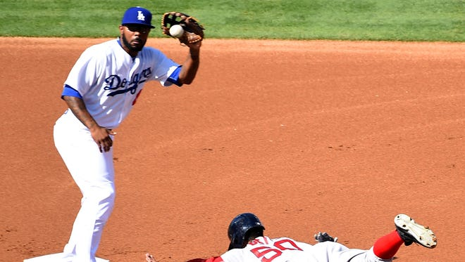 Dodgers left fielder Howie Kendrick takes the throw as Red Sox right fielder Mookie Betts steals second during an August game.