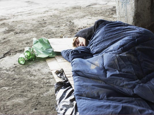 Homeless man sleeping in sleeping bag on cardboard