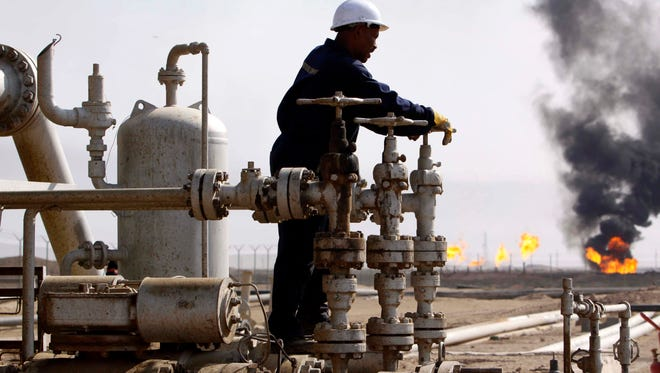 In this Monday, Nov. 9, 2009, file photo, an Iraqi worker operates valves at the Rumaila oil refinery, near the city of Basra, 340 miles southeast of Baghdad, Iraq.
